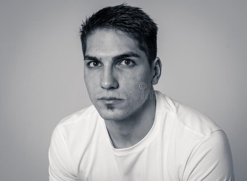 Portrait naturel d'un jeune homme d'une vingtaine d'années qui a l'air et pose avec une expression neutre du visage photo stock
