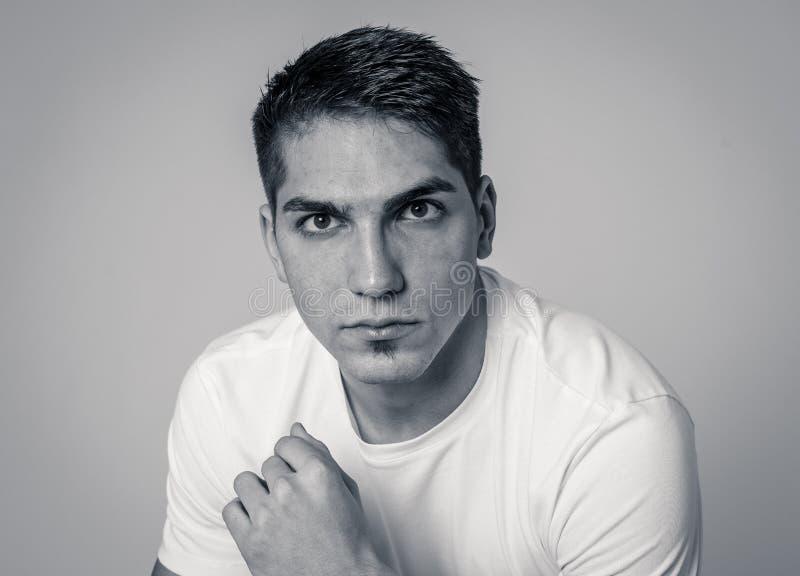 Portrait naturel d'un jeune homme d'une vingtaine d'années qui a l'air et pose avec une expression neutre du visage images libres de droits