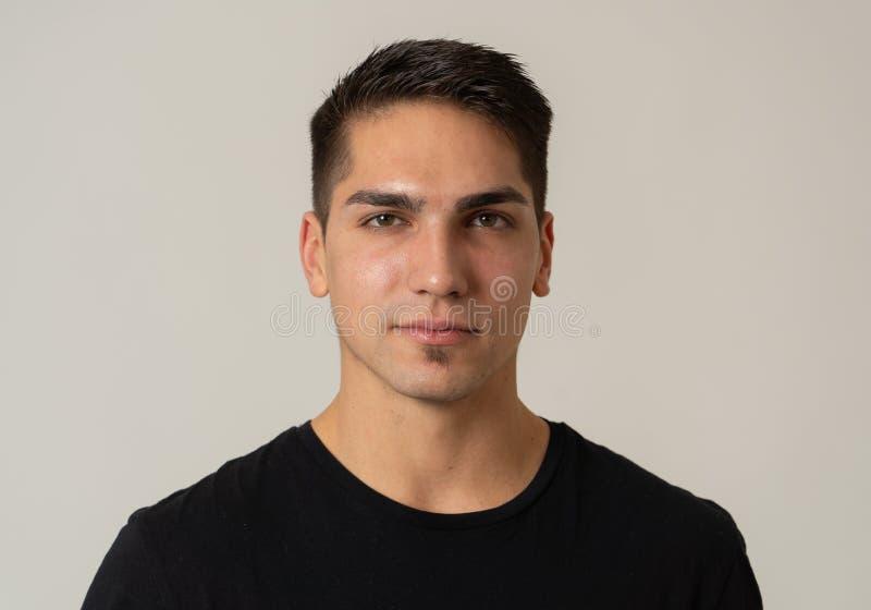 Portrait naturel d'un jeune homme d'une vingtaine d'années qui a l'air et pose avec une expression neutre du visage image libre de droits