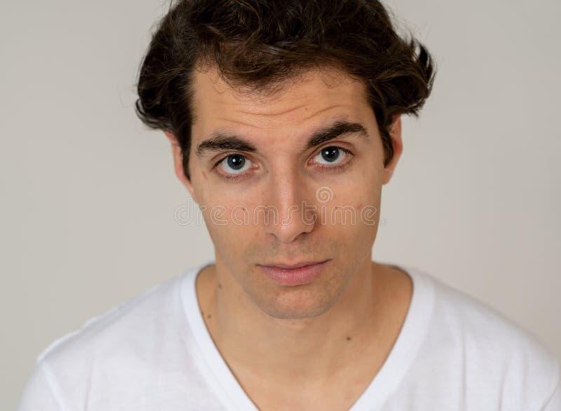 Portrait naturel d'un jeune homme d'une vingtaine d'années qui a l'air et pose avec une expression neutre du visage photos libres de droits