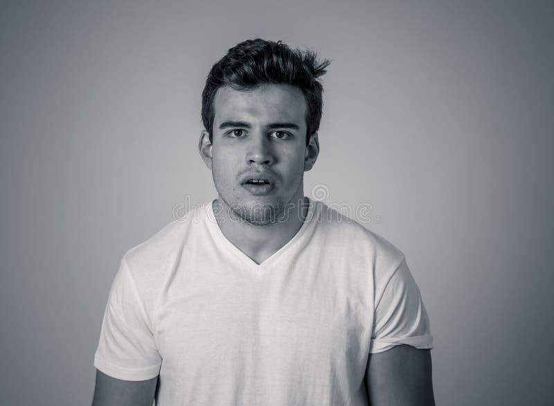 Portrait naturel de jeune homme attirant dans son 20s regardant et posant avec l'expression neutre de visage photo stock