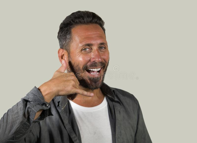 Portrait naturel de jeune homme bel heureux et positif sur son 40s faisant le signe d'appel téléphonique avec des mains et des do photo stock