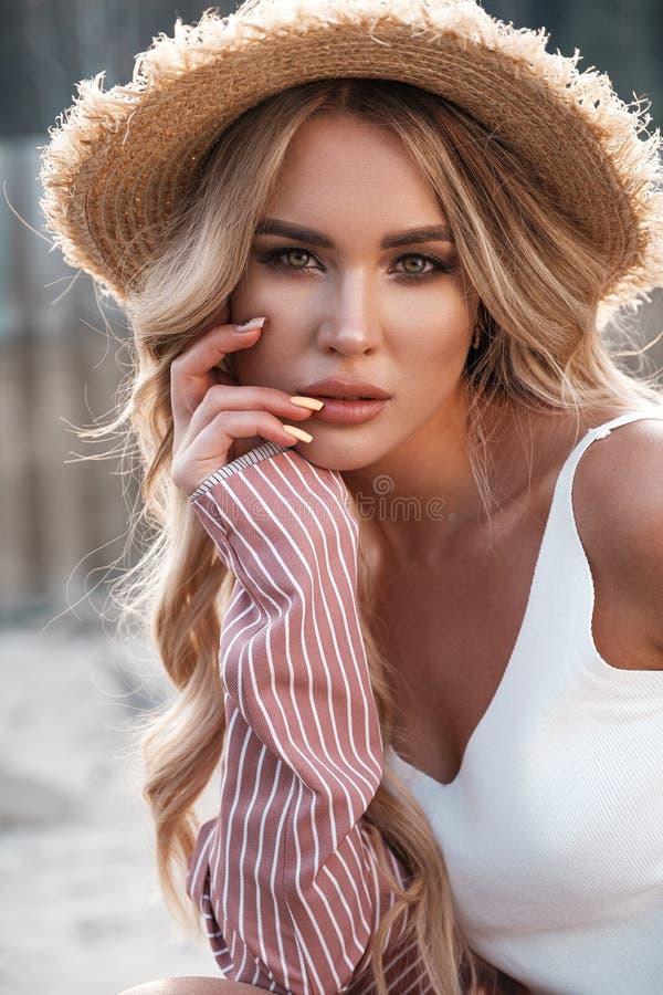 Portrait naturel de mode de vie d'une belle jeune femme magnifique avec de longs cheveux blonds lâches dans un chapeau de paille  photo libre de droits