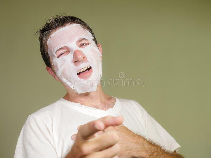Portrait naturel du jeune homme heureux et dr?le appliquant le masque facial de beaut? regardant dans rire de miroir gai se trouv photographie stock libre de droits