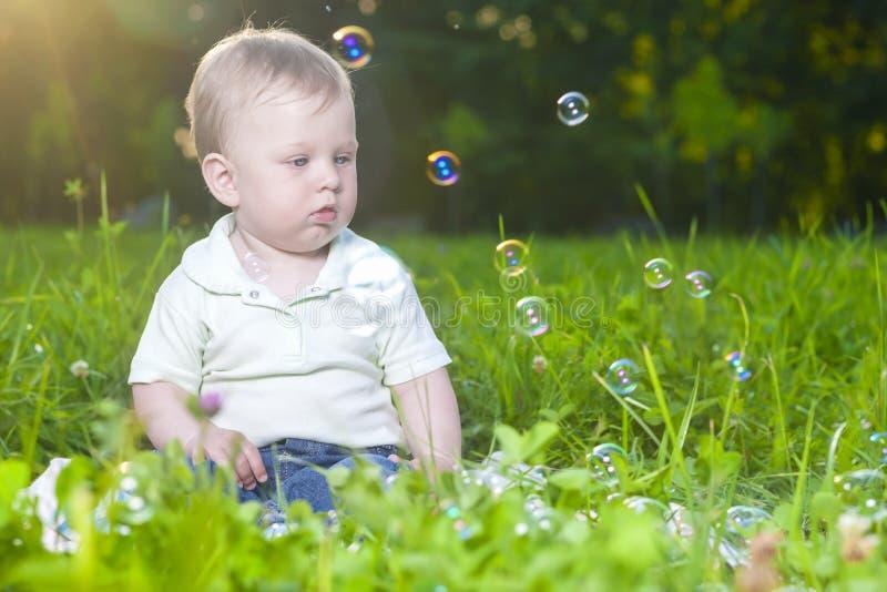 Portrait naturel du petit enfant caucasien mignon d'enfant en bas âge s'asseyant sur l'herbe dehors images libres de droits