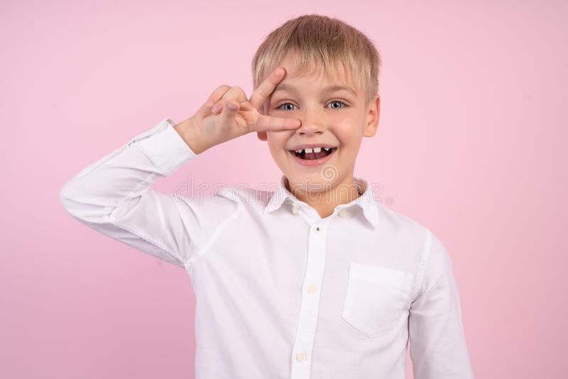 Portrait of naughty little boy smiling and showing peace sign. studio portrait over pink background. wearing white shirt royalty free stock photo
