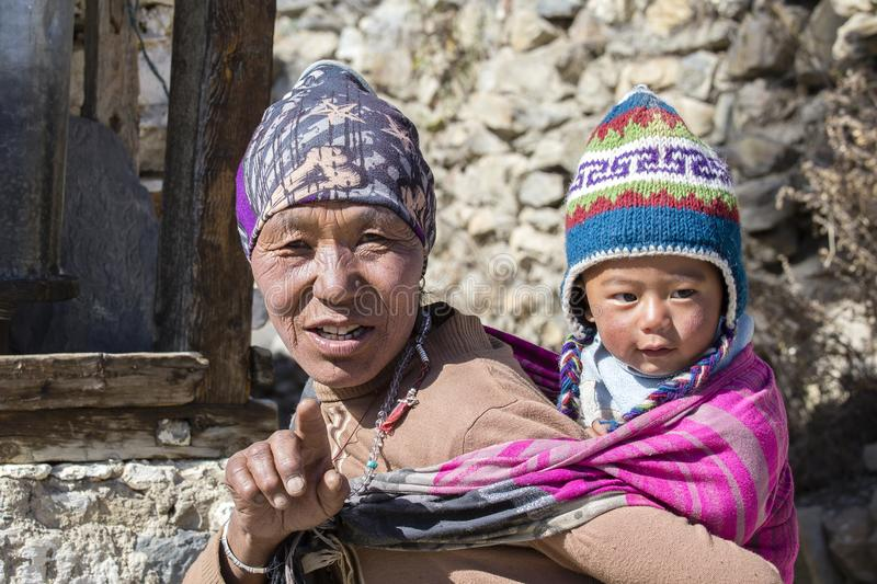 Portrait nepalese mother and child on the street in Himalayan village, Nepal. HIMALAYAS, ANNAPURNA REGION, NEPAL - OCTOBER 17, 2016 : Portrait nepalese mother stock image