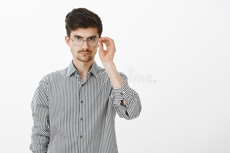 Portrait of nerdy serious-looking male model with beard and moustache, holding rim of glasses, looking focused at camera stock photography