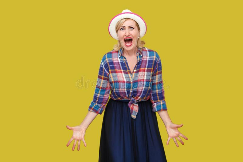 Portrait of nervous aggressive stylish mature woman in casual style with hat standing, raised arms with angry face and looking at royalty free stock photography