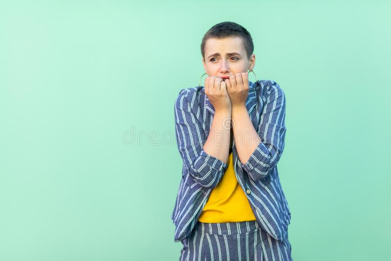 Portrait of nervous handsome beautiful short hair young stylish woman in casual striped suit standing, bitting her nails and panic royalty free stock photo