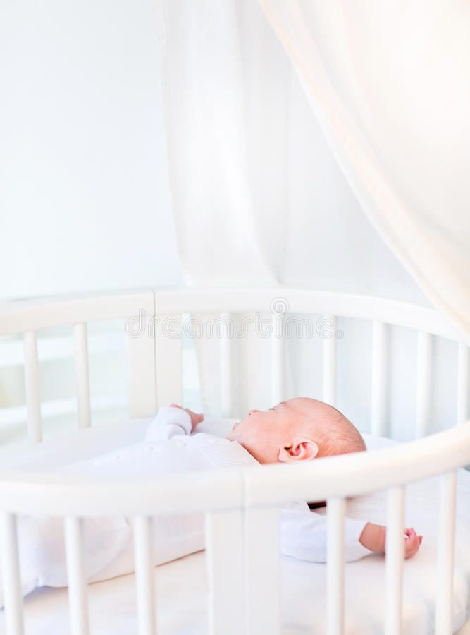 Portrait of a newborn baby boy in white round crib. Portrait of a newborn baby boy sleeping in a white round crib royalty free stock photos