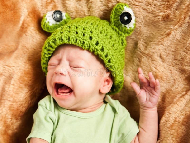 Portrait of a newborn baby cry in a green T shirt and hat. Portrait of a newborn baby cry in green T shirt and hat royalty free stock image