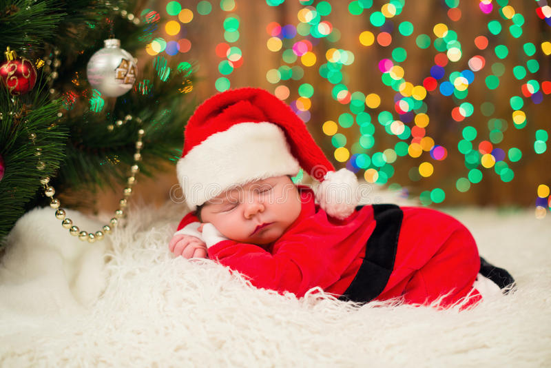 Download portrait of newborn baby in santa clothes lying under christmas tree stock image