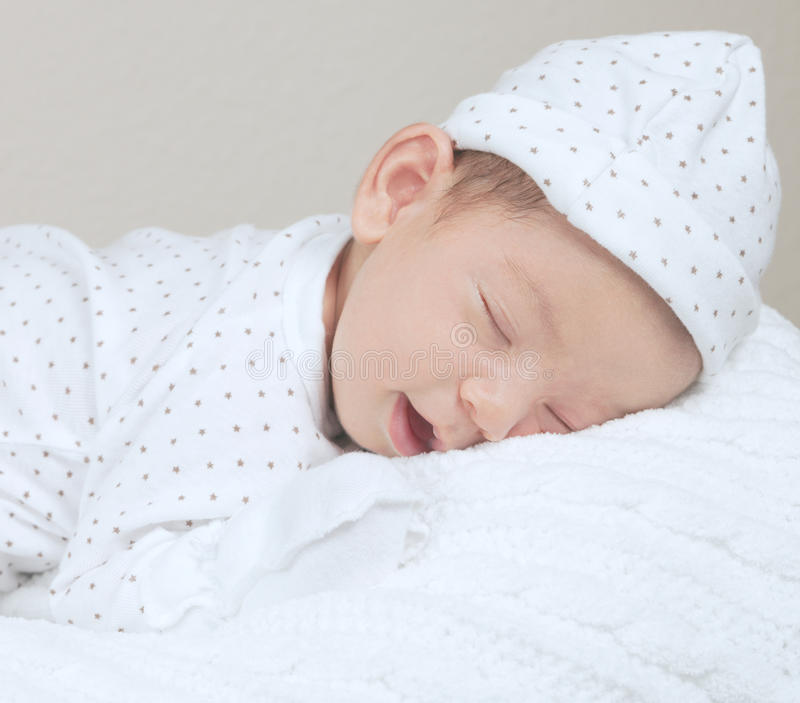 Portrait of newborn smiling and sleeping baby stock image
