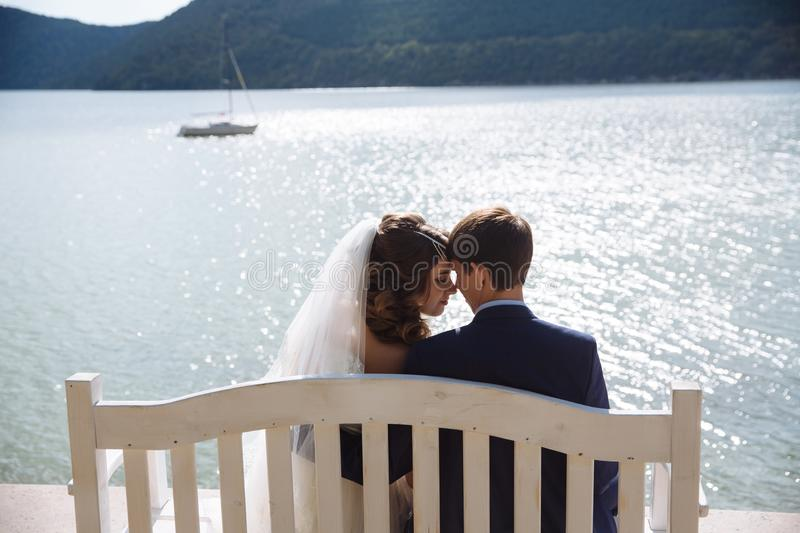 Portrait newlyweds just signed and became husband and wife, came to the embankment, sit on the bench and gently embrace stock image
