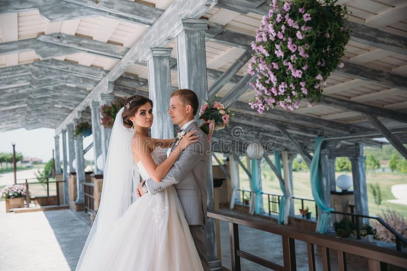 Portrait of newlyweds on wedding day. The groom in a gray suit with a white shirt and a bow tie hugs a beautiful bride. With a luxurious white dress with a veil stock photo