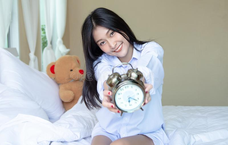 Portrait of nice attractive Asian woman with alarmclock on the bed at the morning. Relax and lifestyle concept royalty free stock image