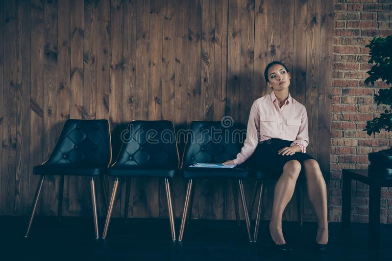 Portrait of nice attractive elegant stylish bored tired lady qualified specialist sitting on chair waiting meeting royalty free stock photo