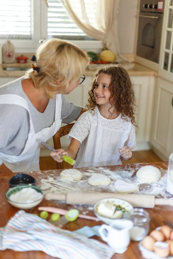 Portrait of adorable curly little girl with her grandmother cooking together at kitchen table. Vertical view. stock photo