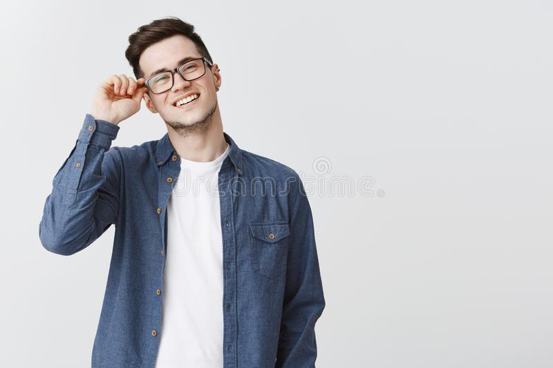 Portrait of nice modern and handsome male student in glasses and blue shirt touching frame of eyewear smiling friendly. And delighted, satisfied with productive stock image