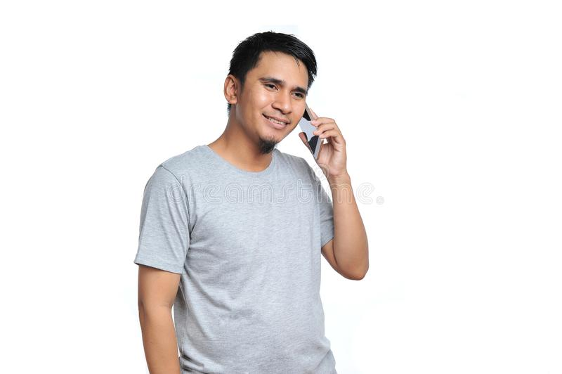 Portrait of nice young asian man talking on mobile phone, speak happy smile royalty free stock images