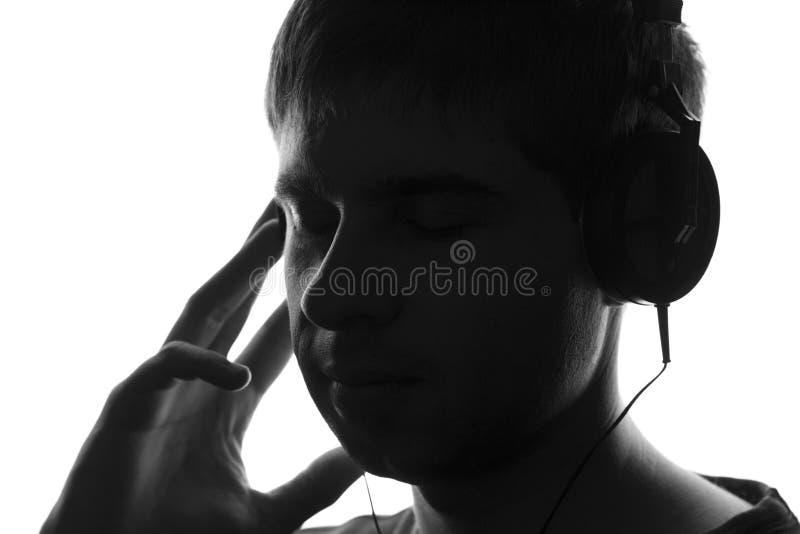 Portrait noir et blanc d'isolement d'un adolescent écoutant la musique dans de grands écouteurs images libres de droits