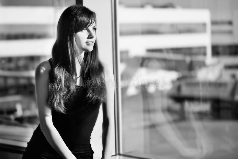 Portrait noir et blanc d'un départ de attente de femme à l'aéroport photographie stock libre de droits