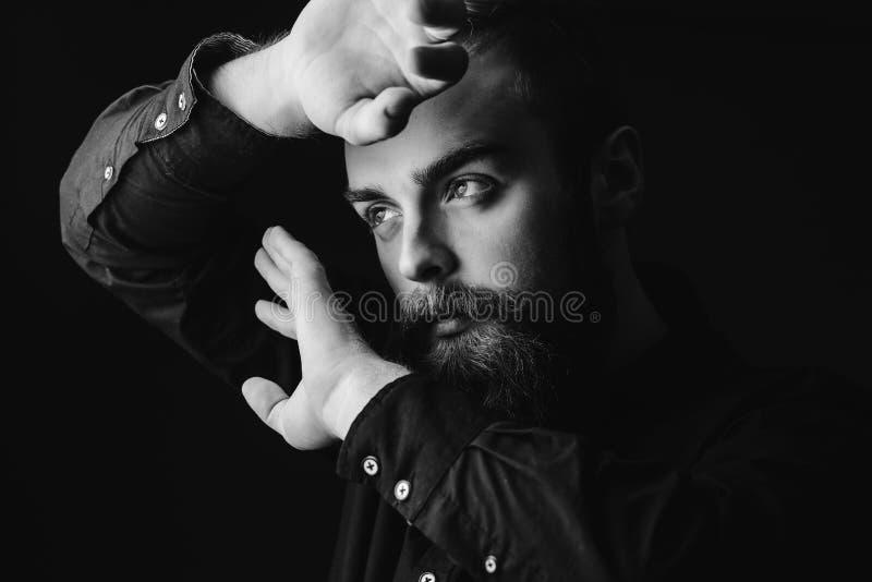 Portrait noir et blanc d'un homme ?l?gant avec une barbe et une coiffure ?l?gante habill?es dans la chemise noire tenant ses main image libre de droits