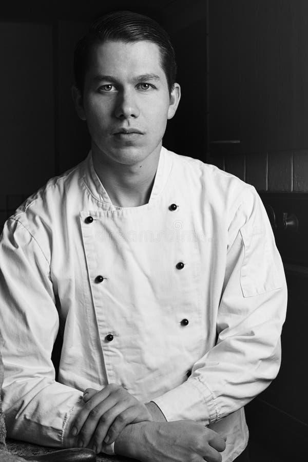 Portrait noir et blanc de gentil et attirant chef d'homme dans l'uniforme dans son restaurant Équipez le chef se tenant dans la c image stock