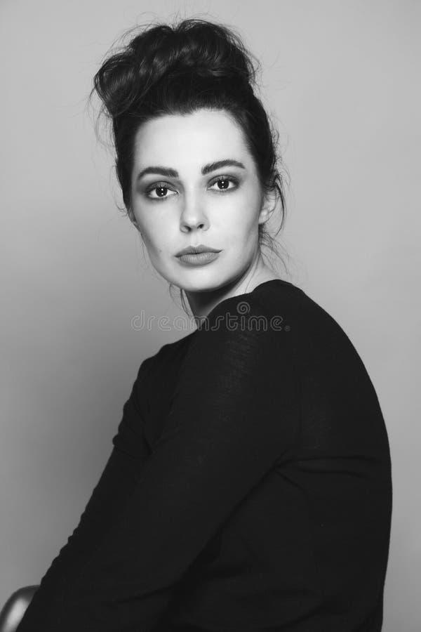 Portrait noir et blanc de jeune belle femme avec le petit pain de fantaisie de cheveux images libres de droits