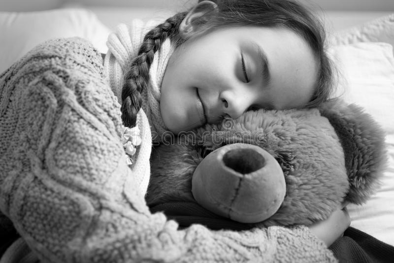 Portrait noir et blanc de la fille rêvante mignonne étreignant le bea de nounours image libre de droits