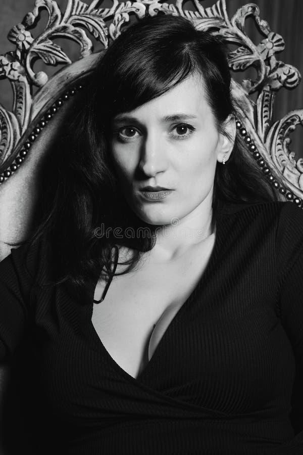 Portrait noir et blanc de la jeune belle position modèle femelle dans la robe sexy noire dans le studio intérieur photo stock