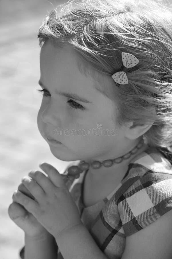 Portrait noir et blanc de profil d'une fille réfléchie triste d'enfant en bas âge avec des perles photographie stock