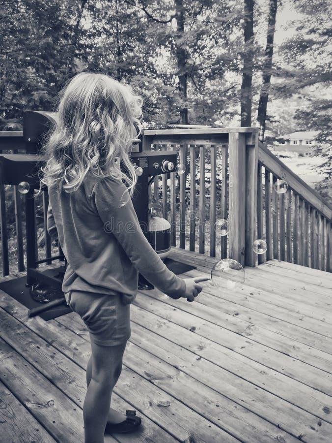 Portrait noir et blanc des bulles de savon sautantes de fille préscolaire blonde photos libres de droits