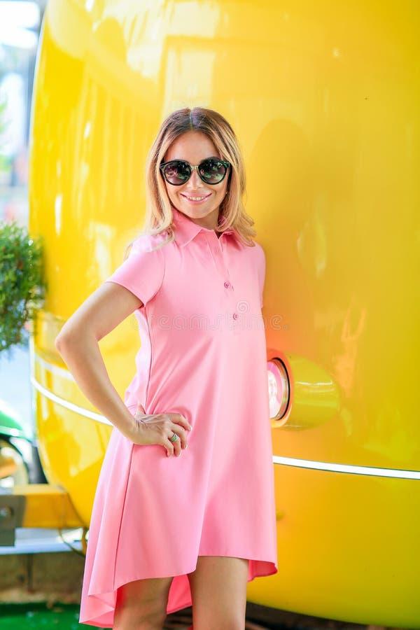 Portrait normal de jeune fille blondy dans un support rose tenant ses mains sur le fond jaune lumineux avec photo stock