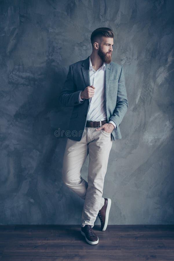 Portrait normal de jeune homme élégant se tenant sur le backgro gris image libre de droits