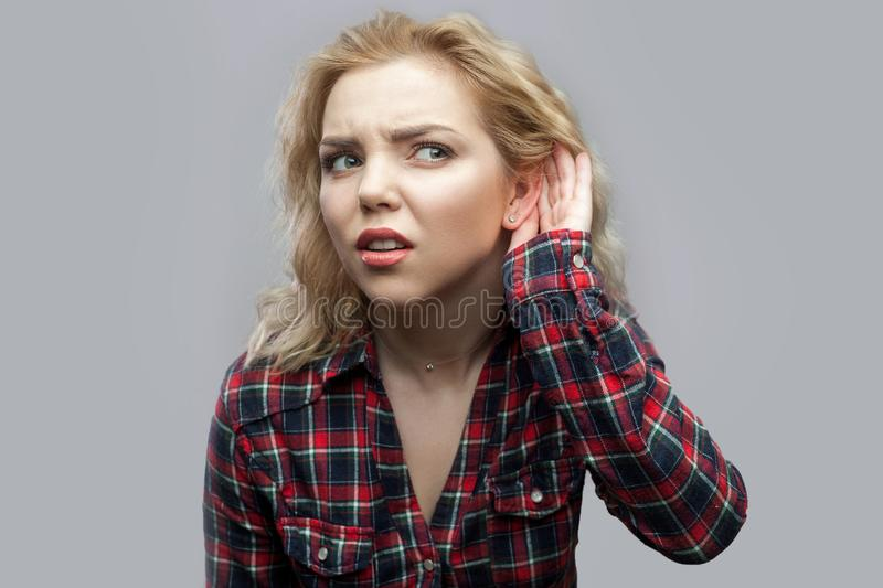 Portrait of nosy beautiful blonde young woman in casual red checkered shirt standing with hand near ear and trying to hear and stock images