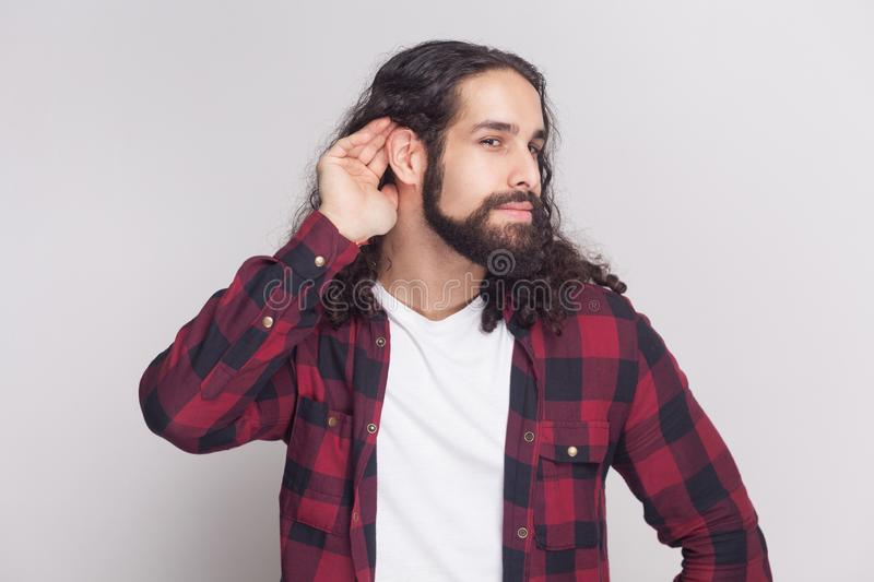 Portrait of nosy man with beard and black long curly hair in casual style, checkered red shirt standing holding hand and ear and. Listening attentive. indoor royalty free stock photos