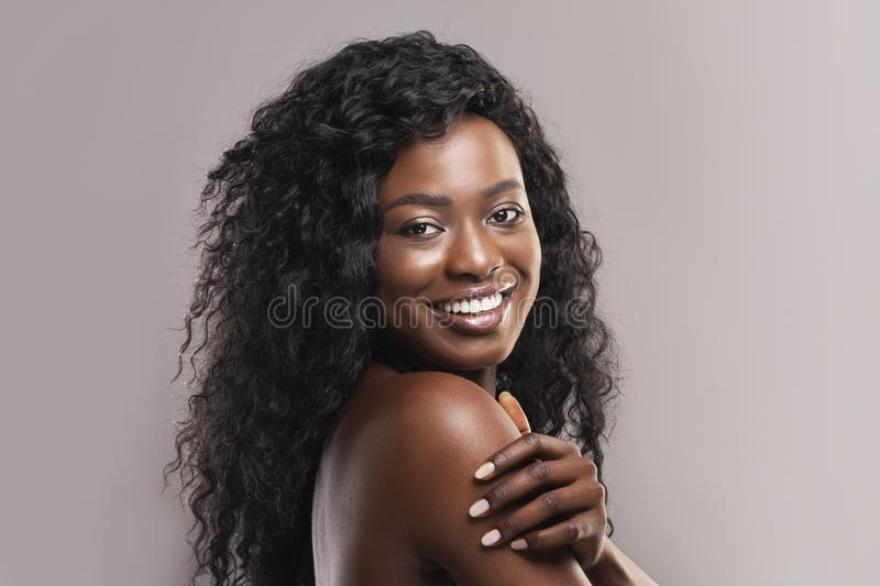 Portrait of nude beautiful afro woman smiling over grey background royalty free stock photos