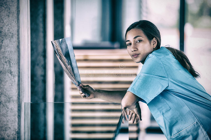 Portrait of nurse holding X-ray report. In hospital stock photo