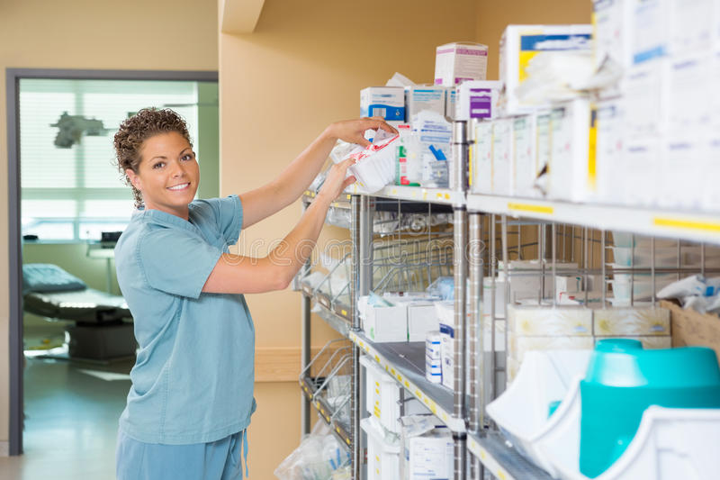 Portrait Of Nurse Working In Storage Room. Portrait of female nurse smiling while working in storage room of cancer hospital stock photos