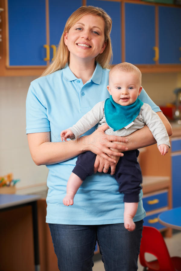 Portrait Of Nursery Worker Holding Baby stock photos