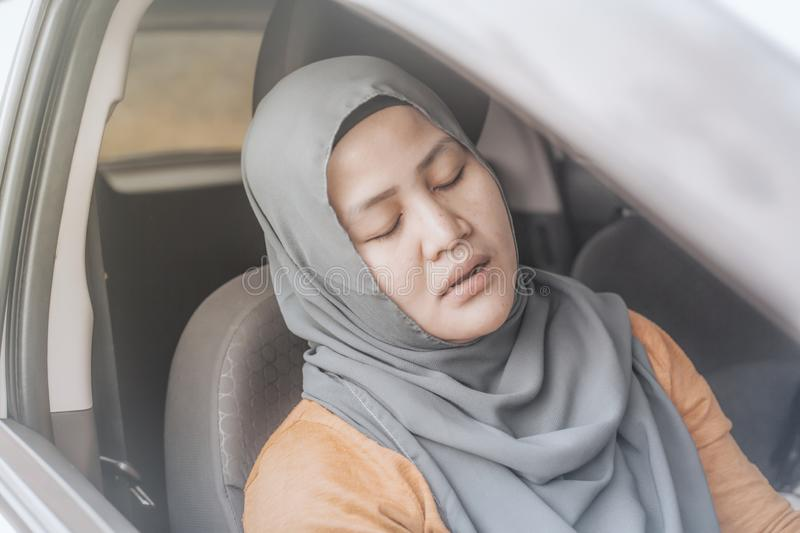 Muslim Lady Slept in Her Car. Portrait o Asian muslim lady slept in her car, tired in the trip, taking nap by the side of the road royalty free stock image