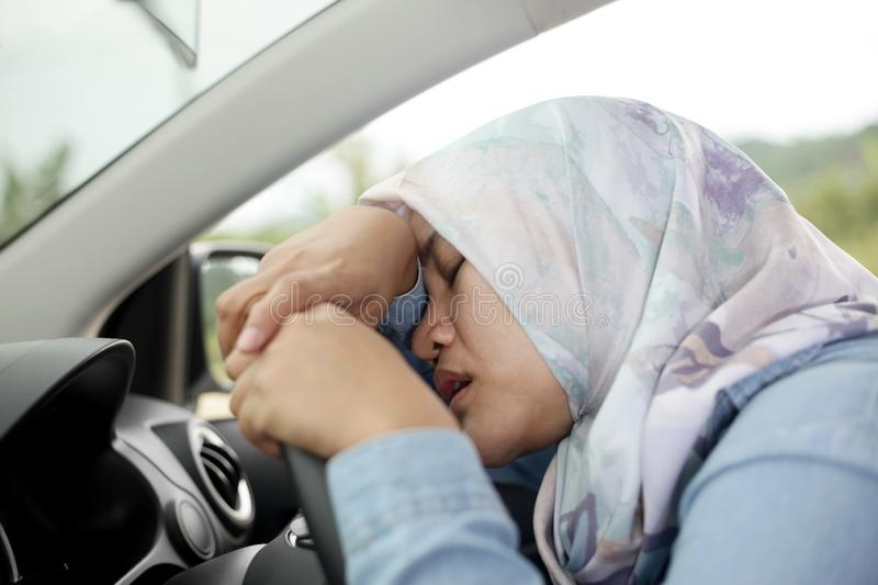 Muslim Lady Slept in Her Car. Portrait o Asian muslim lady slept in her car, tired in the trip, taking nap by the side of the road indonesian malaysian girl royalty free stock photos