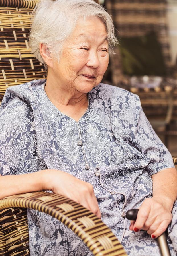 Portrait of a obaasan grandma seated at home, holding a walkin. G stick, feeling happy and smiling. Retired, Japanese descendant stock images