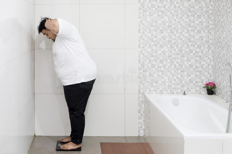 Shocked obese man standing on the scale. Portrait of an obese man looks shocked while standing on the scale. Shot in the bathroom stock photo