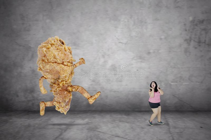 Obese woman looks fearfully with a fried chicken stock photography