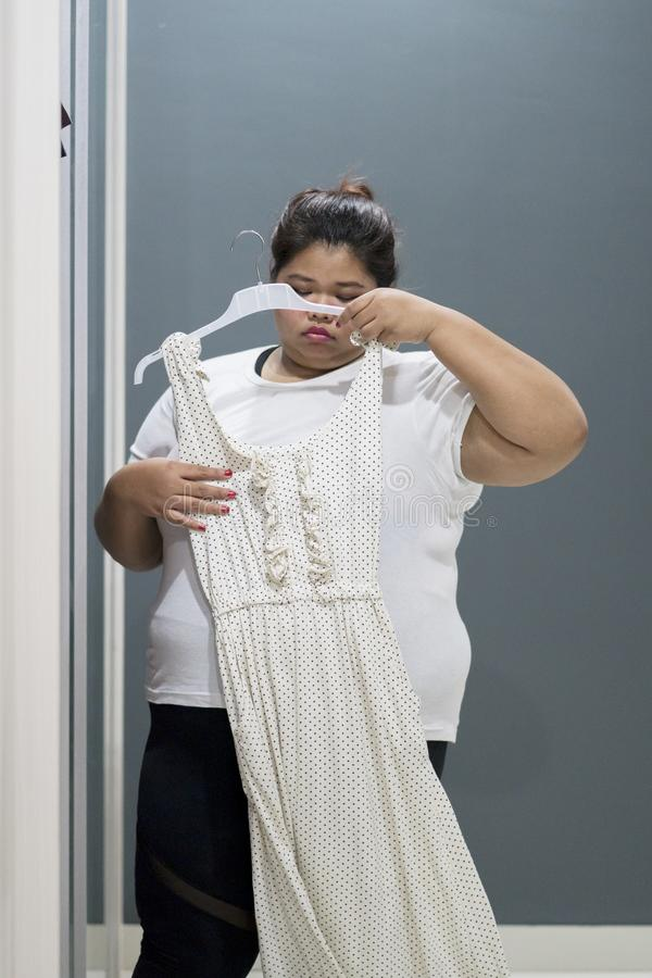Unhappy obese woman trying her old dress royalty free stock photo