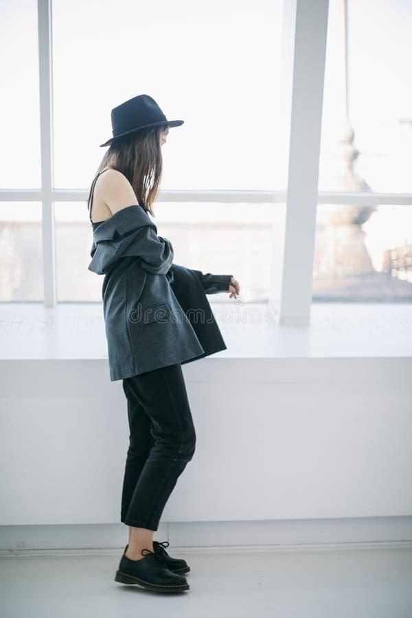 Portrait occasionnel de jeune femme de style de hippie position de fille près de la fenêtre dans la pleine croissance Jour doux H photos stock