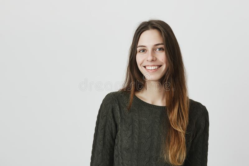 Portrait occasionnel de la jeune fille européenne attirante souriant heureusement avec le regard sincère, d'isolement au-dessus d photographie stock libre de droits
